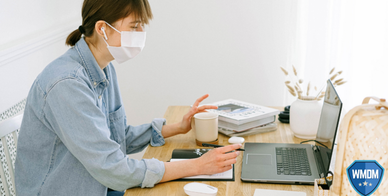 Return to the office - Woman at desk with her mask on.