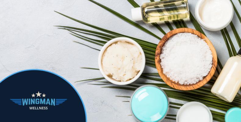 mental health - sugar scrub, cream, essential oils sitting on a palm leaf